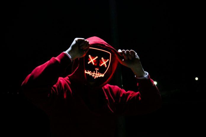 hacker wearing neon mask