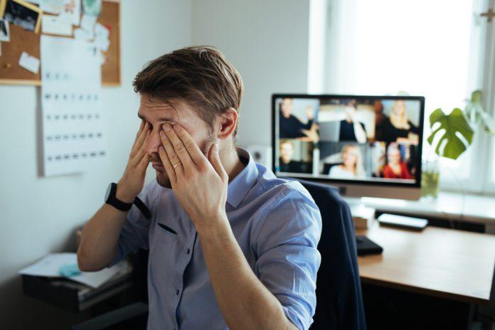 Man rubs eyes during teleconference